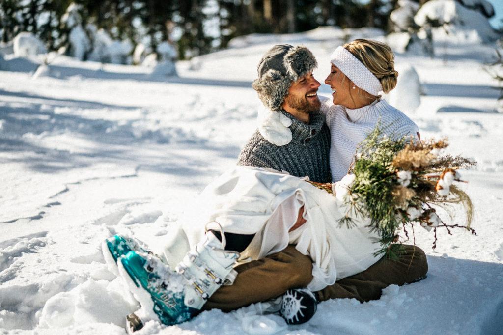 Novomanželé sedící na sněhu na Šumavě